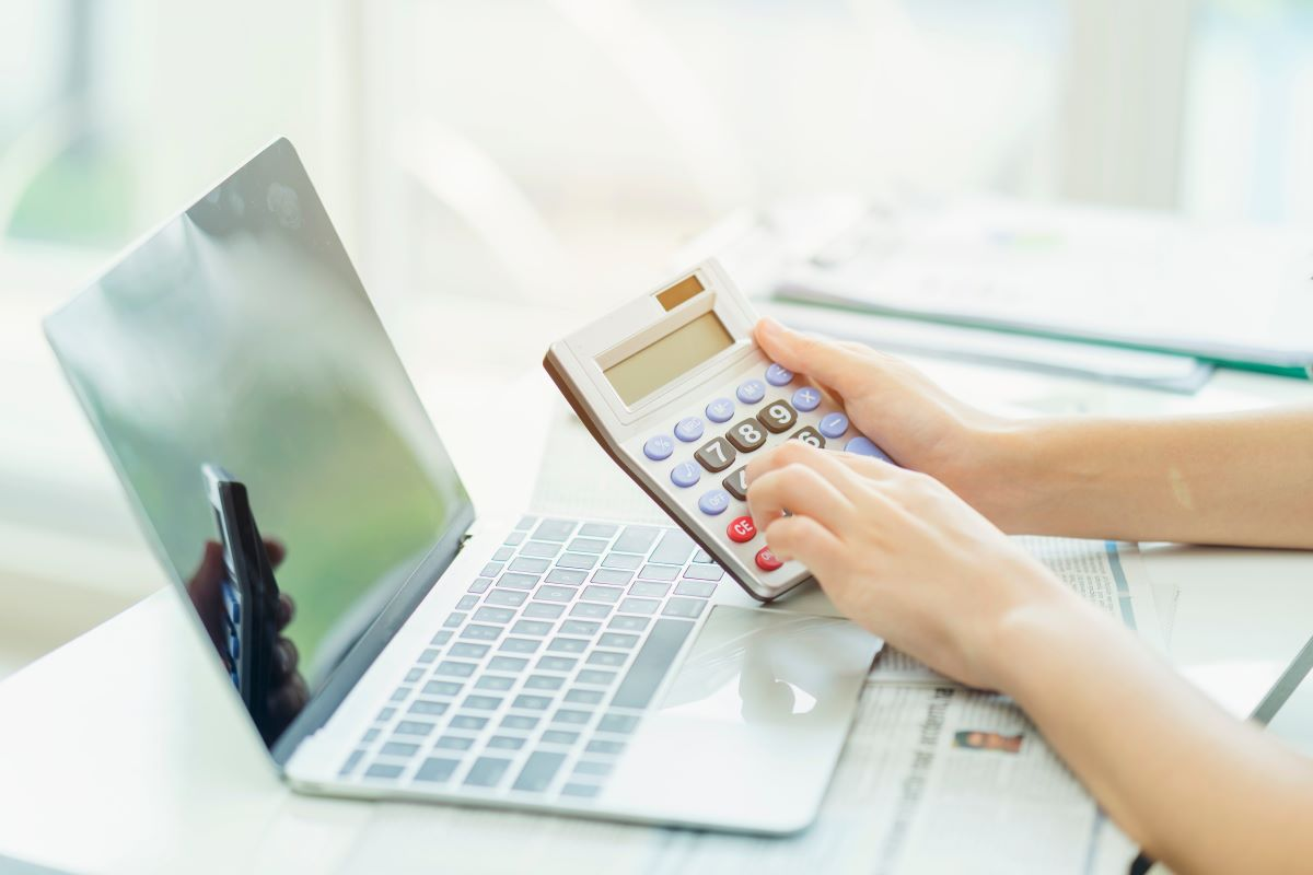 woman using calculator with laptop in front