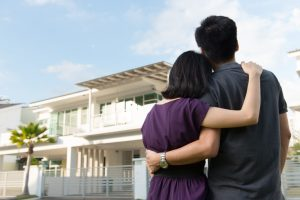 couple holding each other looking at home
